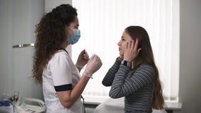 Fachowy cosmetologist w białej lab masce przy pracującym miejscem i kostiumu spotyka klienta - młoda dziewczyna z długie włosy zbiory wideo