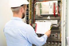 Fachowy elektryk w hardhat czyta elektrycznego plan blisko pulpit operatora na podstacji fotografia stock