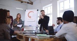 Fachowy energiczny w średnim wieku biznesowego mentora mężczyzny udzielenia doświadczenie z wieloetniczną drużyną przy nowożytnym zdjęcie wideo