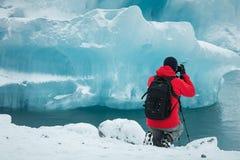 Fachowy fotograf w czerwonym żakiecie i czarnym plecaku bierze obrazek lodowa lód fotografia royalty free