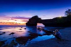 Fachowy fotograf z kamerą i tripod w Tanah udziału świątyni przy zmierzchem, Bali w Indonezja Fotografia Stock