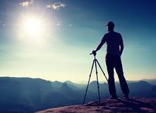 Fachowy fotografa pobyt z tripod na falezie i główkowaniu Marzycielski fogy krajobraz, błękitny mglisty wschód słońca w pięknej d Zdjęcie Stock