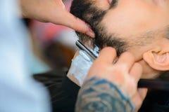 Fachowy fryzjer męski goli brodę jego Obrazy Stock