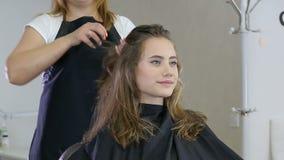 Fachowy fryzjer, stylisty narządzania fryzura dla nastoletniej dziewczyny używa barrette dla załatwiać włosy zbiory