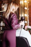 Fachowy fryzjer używa hairdryer podczas gdy włosiany tytułowanie jej żeński klient Piękna młoda kobieta dostaje nowego ostrzyżeni zdjęcia royalty free