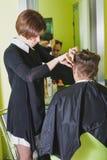 Fachowy fryzjera męskiego tytułowania włosy jego klient Zdjęcia Stock