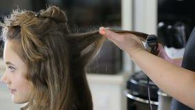 Fachowy fryzjera stylista fryzuje w górę nastoletniego dziewczyna włosy zdjęcie wideo