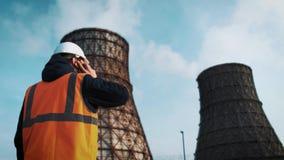 Fachowy inżynier w białym hełmie i kurtek spojrzenia przy fabrycznymi drymbami Dzwoni na telefonie Od deaktywaci zbiory wideo
