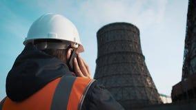 Fachowy inżynier w białym hełmie i kurtek spojrzenia przy fabrycznymi drymbami Dzwoni na telefonie Od deaktywaci zbiory