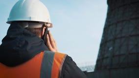 Fachowy inżynier w białym hełmie i kurtek spojrzenia przy fabrycznymi drymbami Dzwoni na telefonie Od deaktywaci zdjęcie wideo