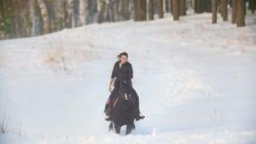 Fachowy jeździec - piękna longhaired żeńska jazda czarny koń przez głębokich śnieżnych dryfów w lesie, wolnym zbiory