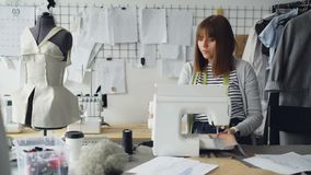 Fachowy kobieta krawczyna przystosowywa szwalnej maszyny zaszywania kawałki tkanina wtedy Kobieta pracuje w świetle zbiory wideo