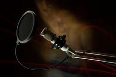 Fachowy kondensatorowy pracowniany mikrofon na czarne twarze, tle i freezelight i Obraz Royalty Free