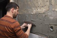 Fachowy konstruktor stosuje kleidło przed kłaść ceramiczny do zdjęcia royalty free