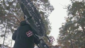 Fachowy krańcowy sportowa rowerzysta znosić grubego rower w górę góra w plenerowym Cyklisty spacer w zima śnieżnym lasowym mężczy zbiory