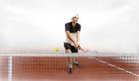 Fachowy mężczyzna trzyma tenisowego kant i piłkę podczas gdy trenujący Obraz Stock