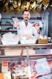 Fachowy męski sklepowy asystent demonstruje rodzaje mięso wewnątrz Zdjęcia Royalty Free
