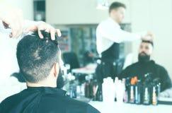 Fachowy męski stylista tworzy ostrzyżenie dla mężczyzna klienta przy hai Zdjęcie Royalty Free