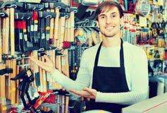 Fachowy młody życzliwy sprzedawcy działanie, ono uśmiecha się i zdjęcia stock