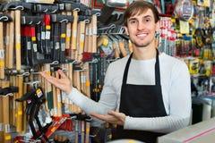Fachowy młody życzliwy sprzedawcy działanie, ono uśmiecha się i fotografia royalty free