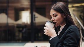 Fachowy młody bizneswomanu odprowadzenie na miastowej ulicznej używa smartphone i napoju kawie Pojęcie: nowy biznes zbiory wideo