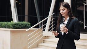 Fachowy młody bizneswomanu odprowadzenie na miastowej ulicznej używa smartphone i napoju kawie Pojęcie: nowy biznes zbiory