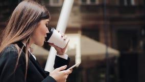 Fachowy młody bizneswomanu odprowadzenie na miastowej ulicznej używa smartphone i napoju kawie Pojęcie: nowy biznes zdjęcie wideo