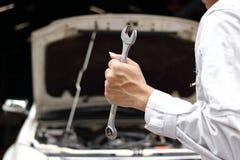 Fachowy młody mechanika mężczyzna w jednolitym mienia wyrwaniu z otwartym kapiszonem przy remontowym garażem tła samochodowy poję fotografia stock