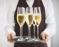 Fachowy męski kelner w jednolitym porcja szampanie dof Zdjęcia Royalty Free