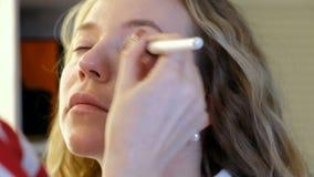 Fachowy makeup artysta pracuje z piękną młodą kobietą zdjęcie wideo