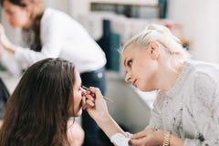 Fachowy makeup artysta robi makeup dla młodej kobiety zdjęcie stock