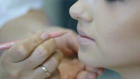 Fachowy makeup artysta robi makeup młodej kobiety wargom z warga ołówkiem zbiory wideo