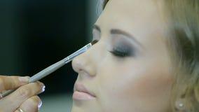 Fachowy makeup artysta stosuje oko połysku młodej kobiety powiekę zbiory