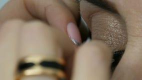 Fachowy makeup artysta wtyka sztuczne rzęsy na niebieskich oczach dorosła w średnim wieku kobieta zamknięta w górę widoku zbiory