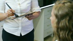 Fachowy makijażu artysta stosuje śmietanki bazę blondyny długo fryzuje włosy i niebieskie oczy modelują skórę zbiory wideo