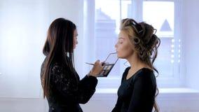 Fachowy makijażu artysta stosuje makeup na kobiety ` s twarzy obrazy stock