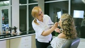 Fachowy makijażu artysta stosuje tonalną śmietankę blondyny długo fryzuje włosy i niebieskie oczy modelują skórę Kształtująca twa zbiory wideo