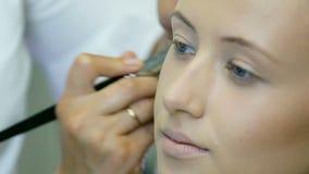 Fachowy makijażu artysta stosuje tonalną śmietankę blondyny długo fryzuje włosy i niebieskie oczy modelują skórę Kształtująca twa zbiory