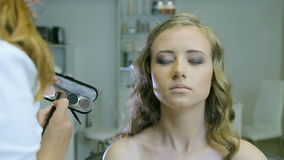 Fachowy makijażu artysta stosuje tonalną śmietankę blondyny długo fryzuje włosy i niebieskie oczy modelują skórę zdjęcie wideo