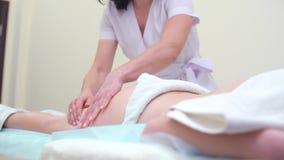 Fachowy masażysta w mundurze robi antemu celulitisu masażowi dla młodej kobiety zbiory
