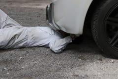 Fachowy mechanika mężczyzna w bielu munduru łgarskim puszku i naprawianie pod samochodem Samochodowy utrzymania pojęcie zdjęcia stock