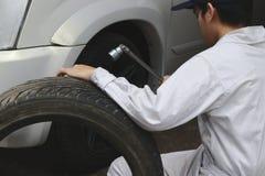 Fachowy mechanika mężczyzna w bielu munduru mienia oponie przy remontowym garażu tłem i wyrwaniu Asekuracyjny samochodowy pojęcie fotografia royalty free