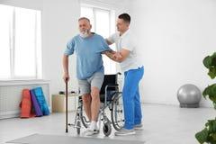 Fachowy physiotherapist pracuje z starszym pacjentem zdjęcia stock