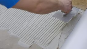 Fachowy pracownik kłaść płytki na podłodze przy budową w górę budowniczego stawia beton na podłodze zbiory