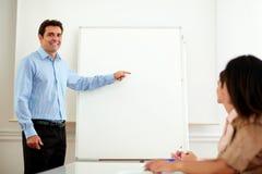 Fachowy przystojny mężczyzna wskazuje przy whiteboard obraz royalty free