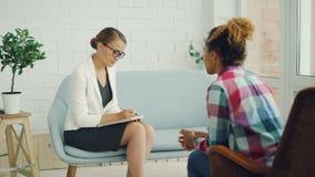 Fachowy psycholog słucha skołatany amerykanin afrykańskiego pochodzenia dziewczyny pacjent i pisze w notatniku podczas gdy ona zbiory wideo