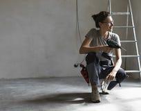 Fachowy repairwoman pozuje świder i trzyma obraz royalty free