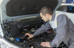 Fachowy samochodowy mechanik pracuje w auto remontowej usługa z laptopem zdjęcie royalty free