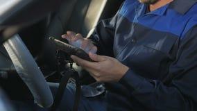 Fachowy samochodowy mechanik pracuje w nowożytnej auto remontowej usługa i sprawdza silnika zbiory