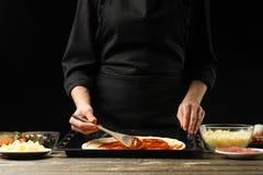 Fachowy szef kuchni przygotowywa Włoską pizzę, rozprzestrzenia pomidorowego kumberland Na czarnym tle, horyzontalna fotografia Po fotografia stock